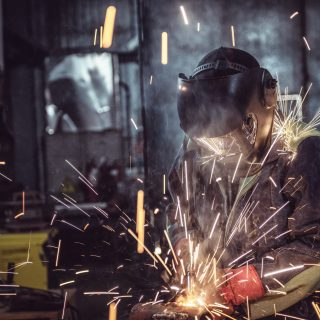 Industrial Worker laborer at the factory welding steel structure