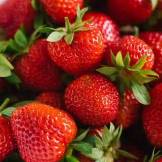 Fresh red organic strawberries closeup, background of berries