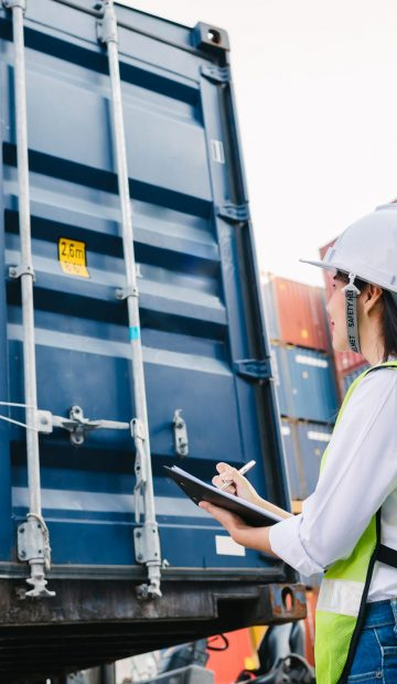 Asian staff woman checking container box for logistic Import Export in dock