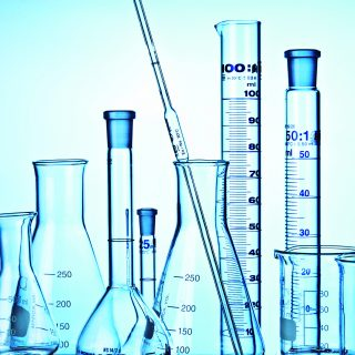 Flask, Measuring Cylinders, Glass Mug and pipette in laboratory.