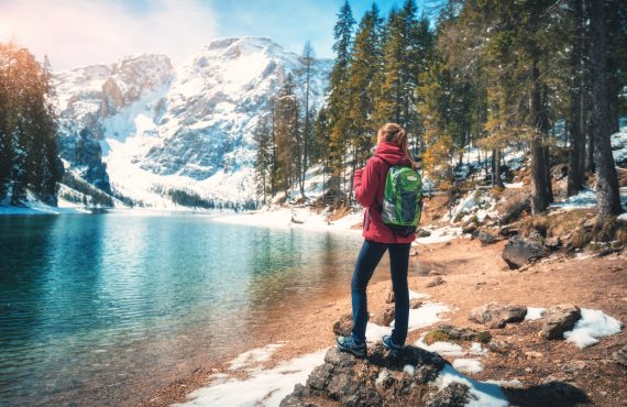 woman with backpack on the stone near lake with azure water